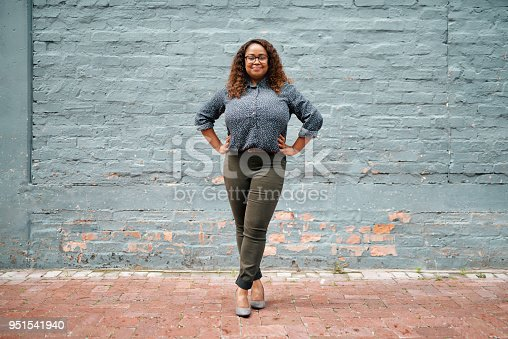 Portrait of an attractive and confident young woman standing against a gray wall outside