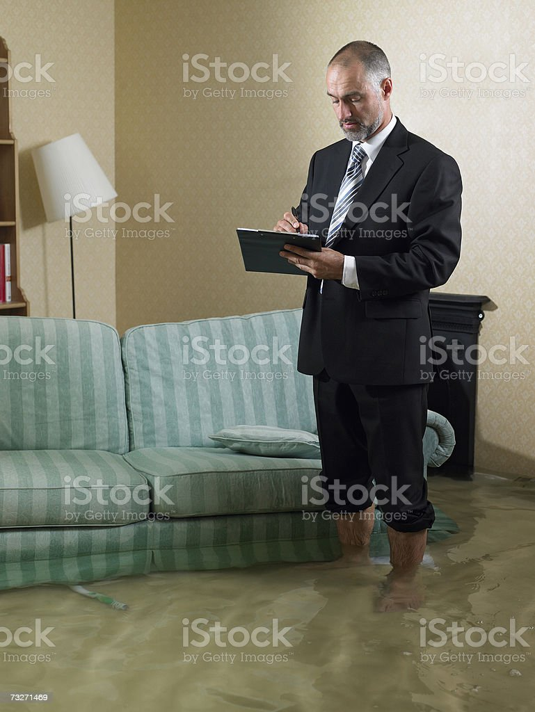 Claims adjuster standing in flooded living room stock photo