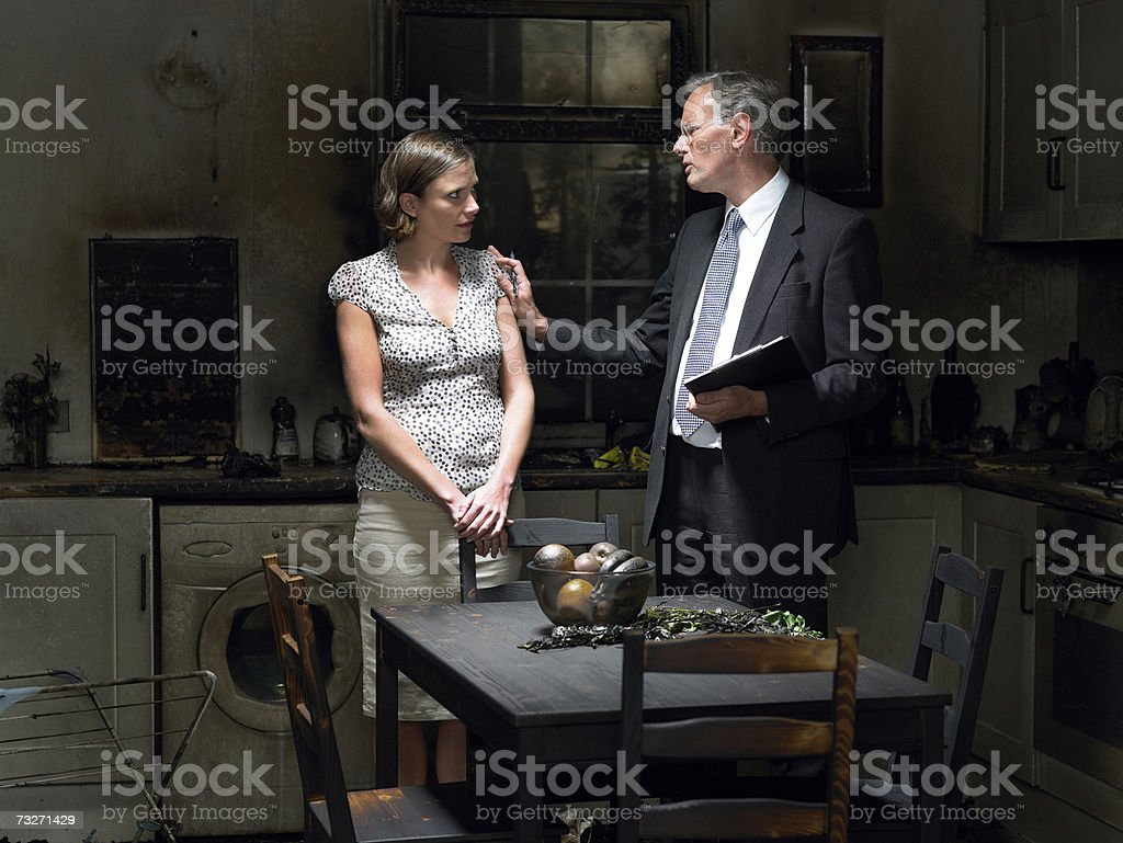 Claims adjuster talking to woman in kitchen damaged by fire royalty-free stock photo