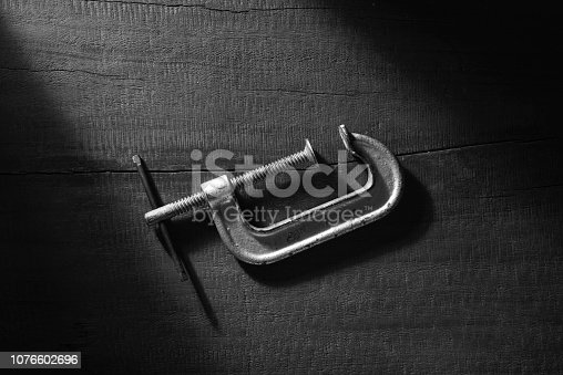 Clamp compression tool isolated on diagonal on wooden background