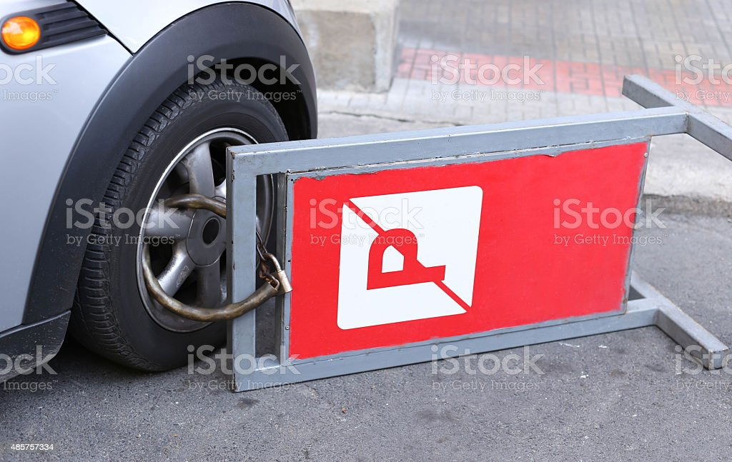 clamped front wheel of illegally parked car stock photo