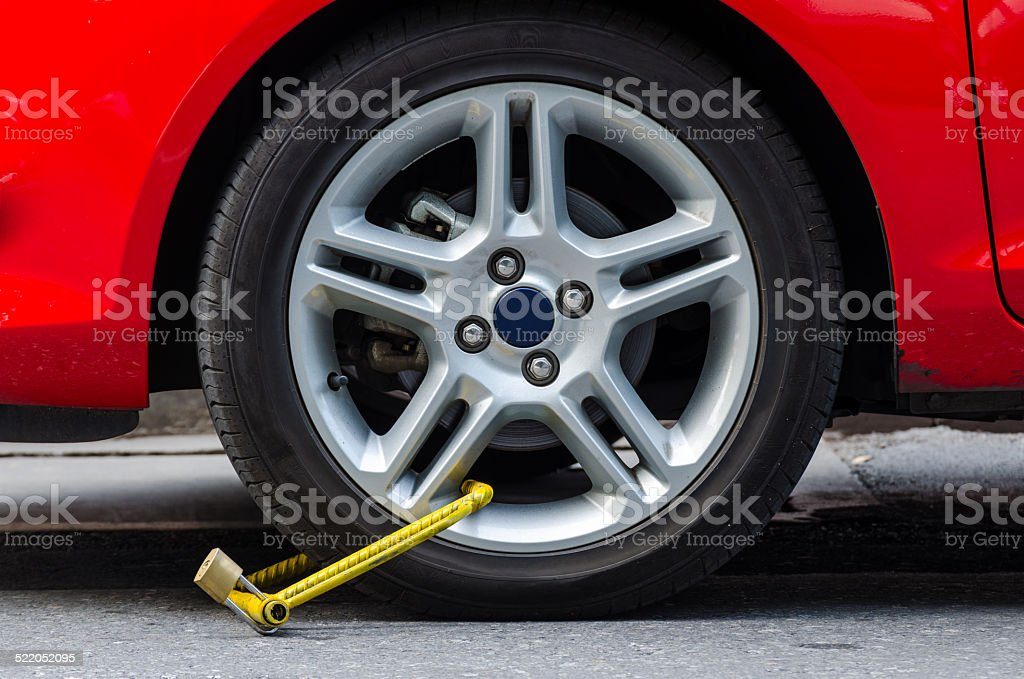 Clamped wheel of illegally parked car stock photo