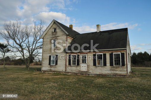 An old clapboard farmhouse stands abandoned. Front porch is gone, foundation is brick and many of the roof shingles are blown away. The small farm way of life seems to have blown away too.