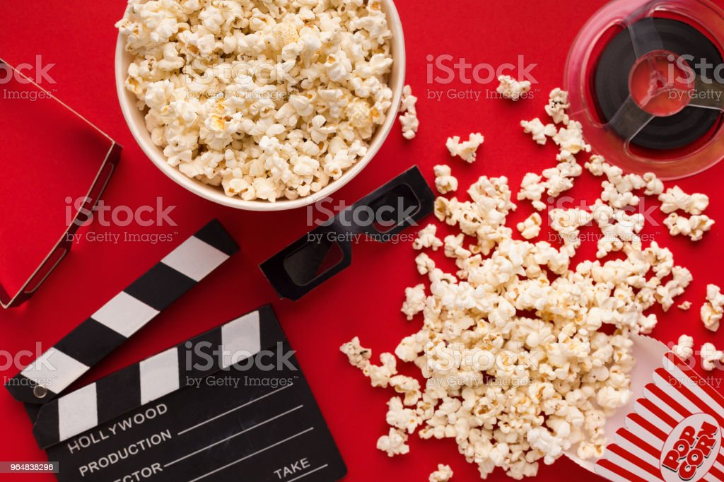 Clapperboard, 3D glasses and popcorn on red background royalty-free stock photo