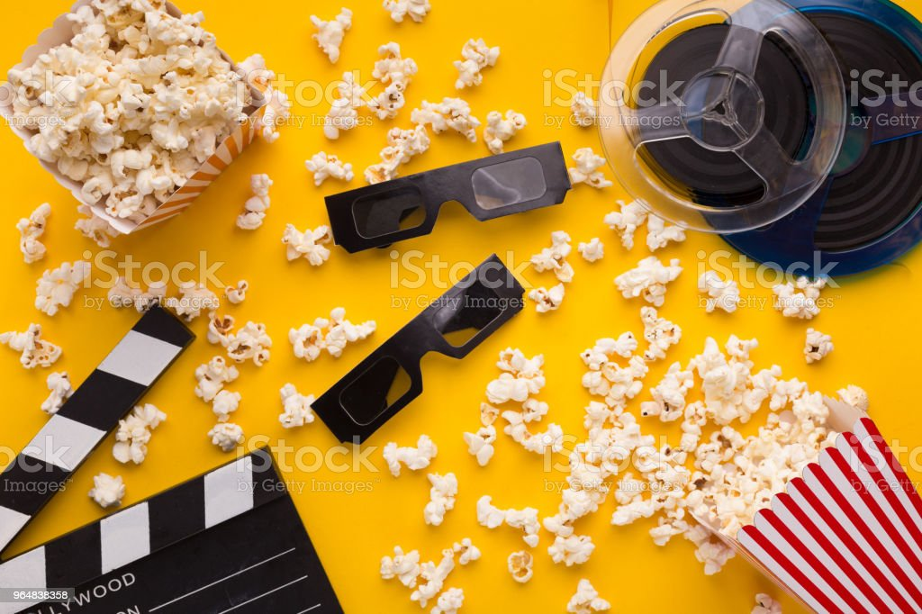Clapperboard, 3D glasses and popcorn on yellow background royalty-free stock photo