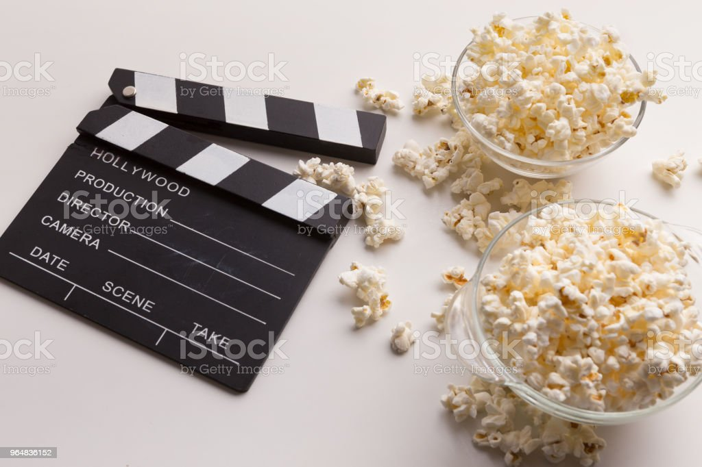 Clapperboard and popcorn on white background royalty-free stock photo