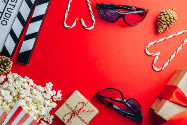 clapperboard, popcorn, 3d glasses, cande cane, christmas gifts in a red paper background. flat lay. top view. christmas concept - christmas movie foto e immagini stock