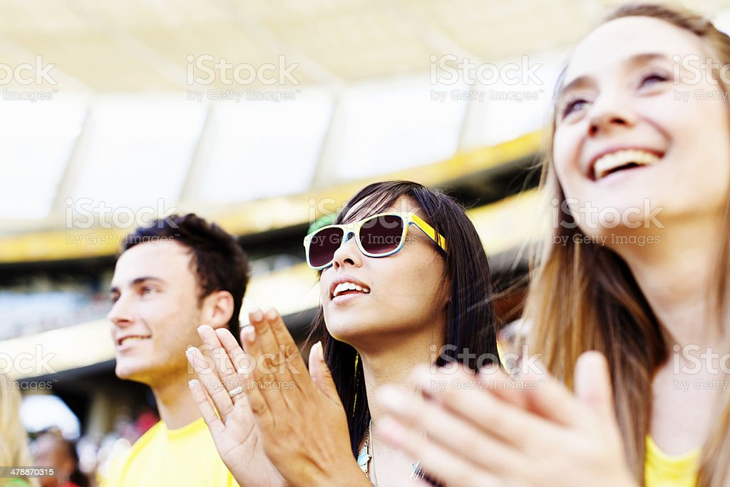 Clapping football fans support their team, smiling stock photo