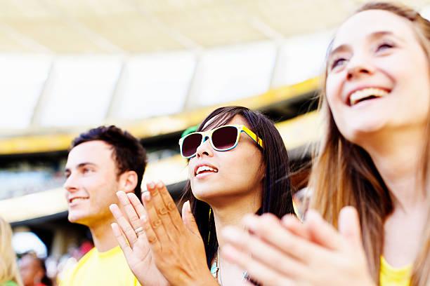 klatschen fußball-fans ihre mannschaft unterstützen, lächeln - spielerfrauen stock-fotos und bilder