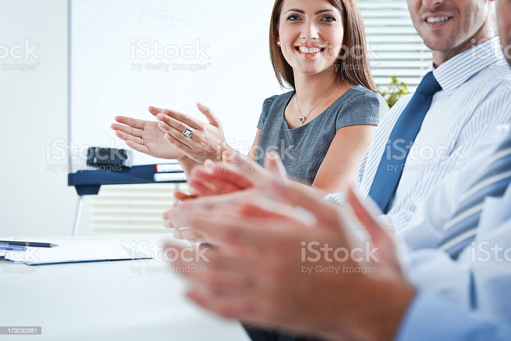 Clapping hands Happy business people clapping hands during business meeting. Focus on the businesswoman smiling at the camera. Admiration Stock Photo