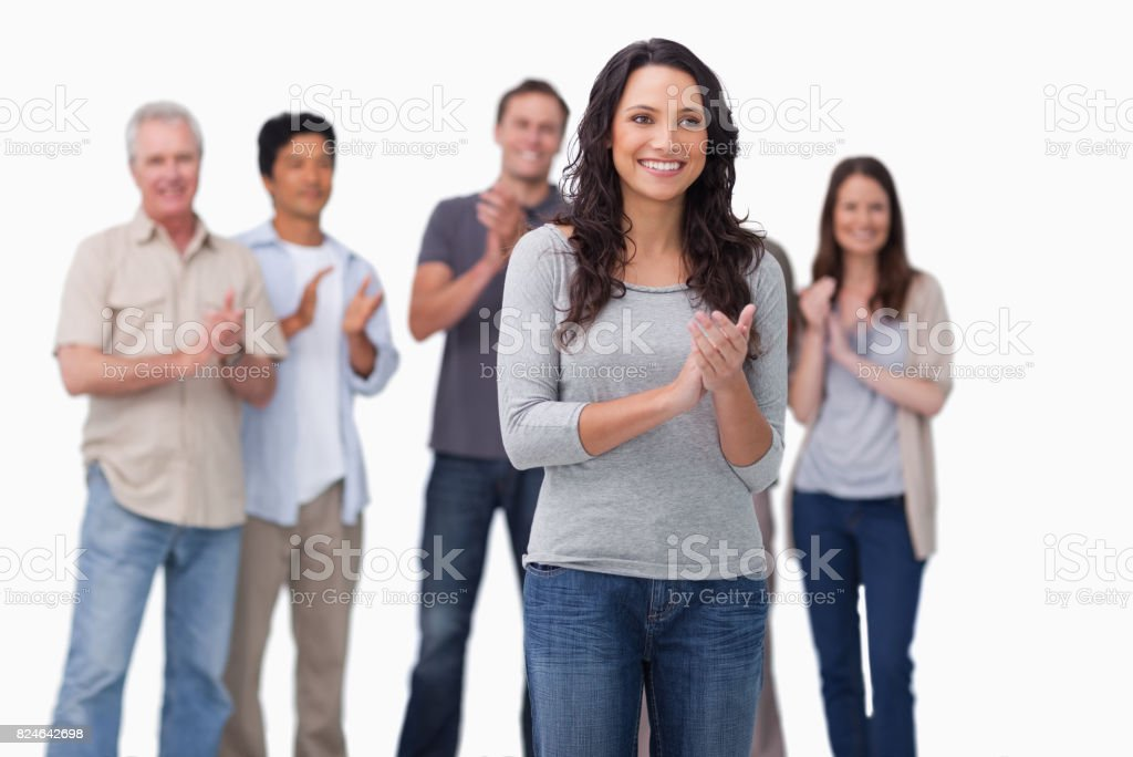 Clapping young woman with friends behind her stock photo