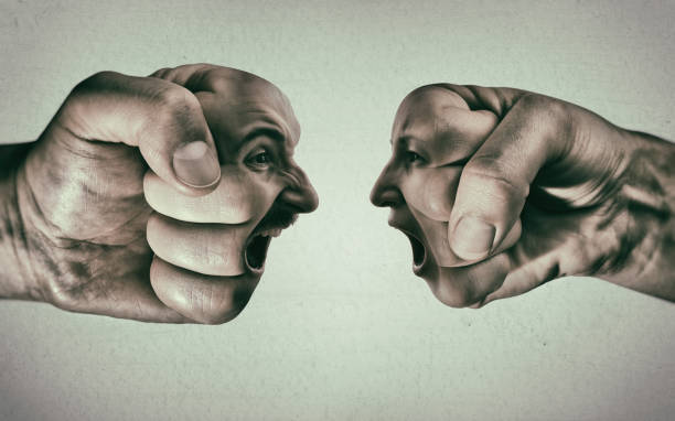 Clash of two fists on light background stock photo