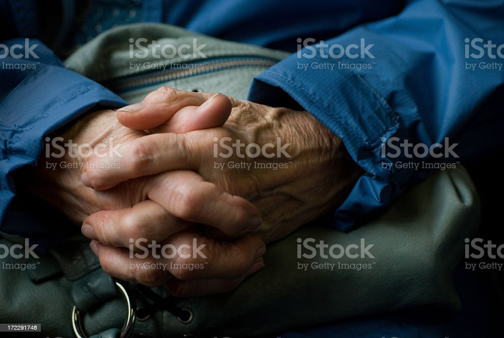 Clasped hands of a senior wearing blue sleeves stock photo