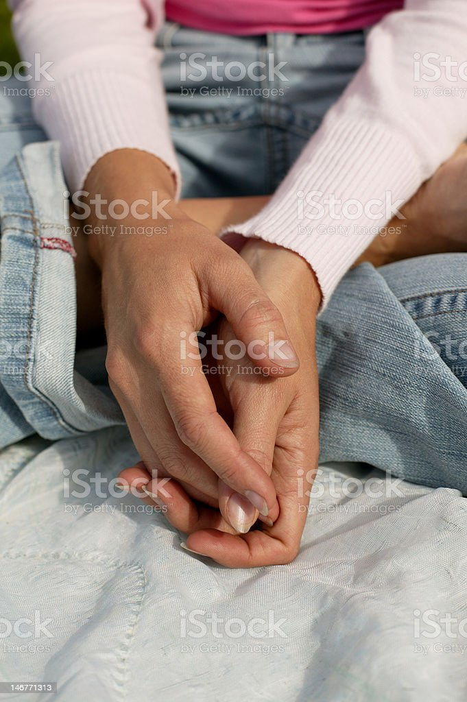 Clasped hands resting on crossed legs stock photo