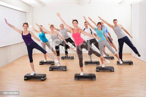 istock Class doing aerobics balancing on boards 160495583