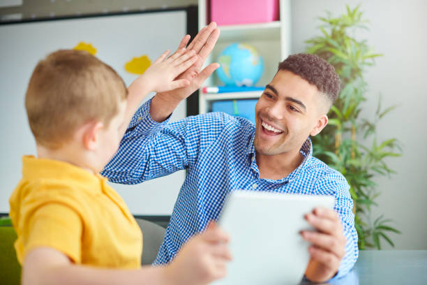 class high five schoolboy with trainee teacher teacher stock pictures, royalty-free photos & images