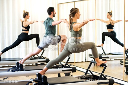 istock Class in a gym doing pilates standing lunges 1171254686