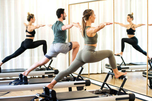 class in a gym doing pilates standing lunges - metodo pilates foto e immagini stock