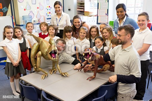 Puppet dinosaurs in the classroom. The class wearing school uniform gather behind a table and smile at the camera. Their teacher stand in the background.