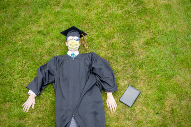class of 2020 graduate laying on ground with diploma - sdominick stock pictures, royalty-free photos & images