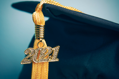 A close up of a 2021 charm on a tassel hanging from a graduation cap.