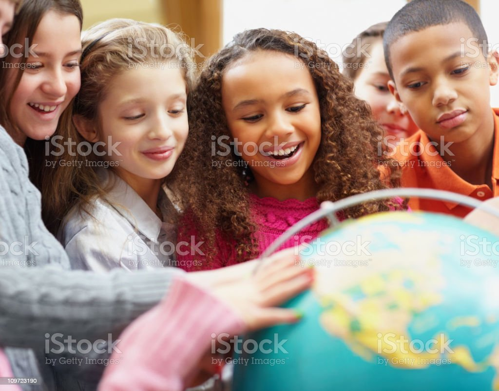 Class of geography students looking at a globe royalty-free stock photo