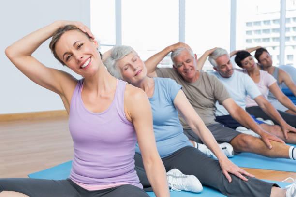 klasse dehnung hals in zeile am yoga-kurs - hals übungen stock-fotos und bilder