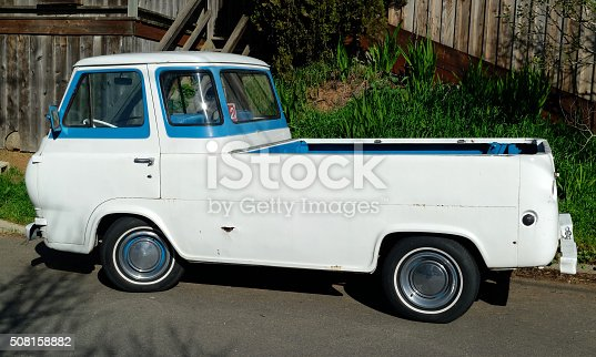 Classic 1960s Ford Econoline van parked in residential neighborhood.