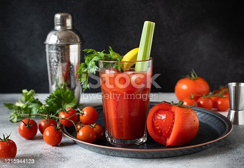 istock Classic alcoholic cocktail Bloody Mary with ice, lemon and celery. Cocktail ingredients and bar tools on a gray table and black background 1215944123