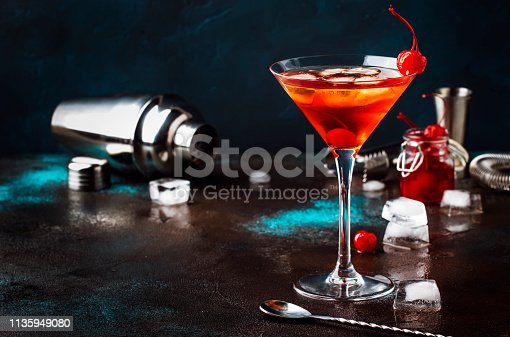 Classic alcoholic cocktail Manhattan with bourbon, red vermouth, bitter, ice and cocktail cherry in glass, night bar background, place for text, selective focus