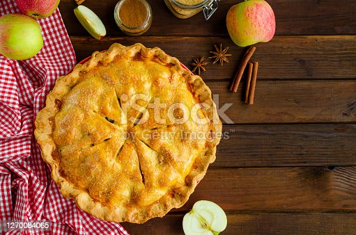 Classic American apple pie with cinnamon on a dark wooden background. Rustic style. Top view, copy space