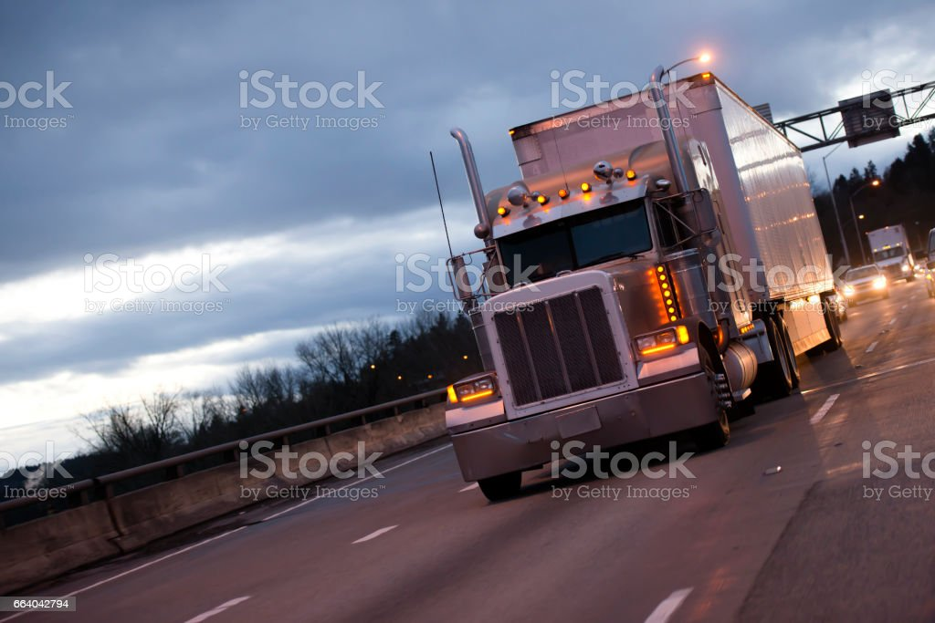 Classic american big rig semi truck tractor and reefer trailer on evening twilight highway road stock photo