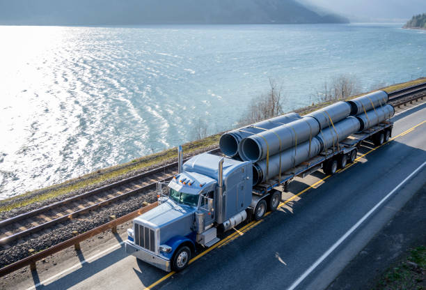 Classic American big rig semi truck transporting big plastic pipes on flat bed semi trailer driving on the road along the river in Columbia River Gorge stock photo