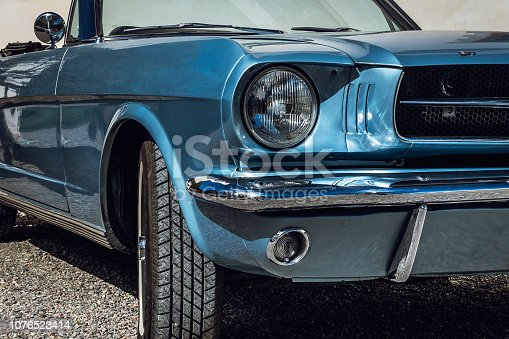 Partial close up of a light blue metallic colored classic car from the sixties shining in bright sunshine