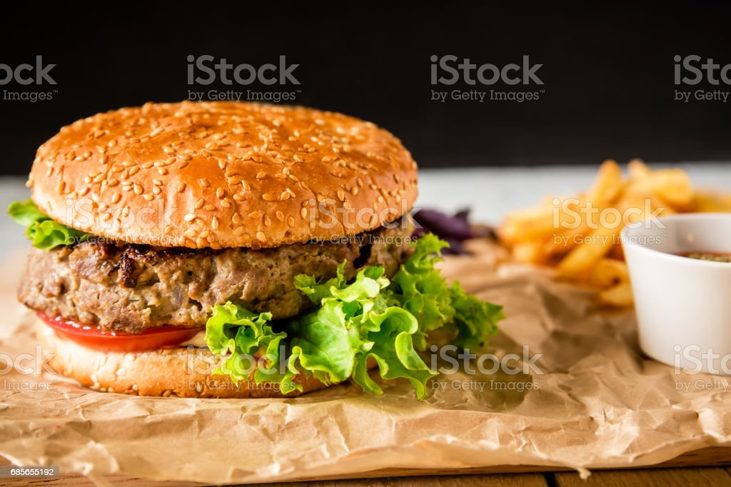 Classic american hamburger with beef and tomato sauce on dark background. Tasty food 免版稅 stock photo