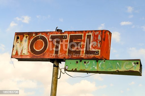 A derelict Route 66 classic motel sign against a cloudy sky.