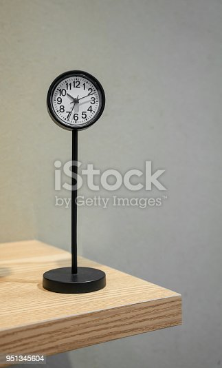 istock Classic analog clock with metal stand on wooden shelf 951345604