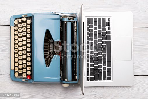 Modern Laptop Computer with Antique Typewriter on wooden desk