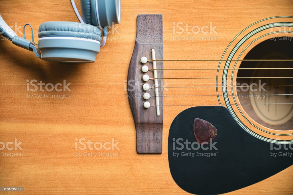 Classic and music style. Acoustic guitar background with headphone...
