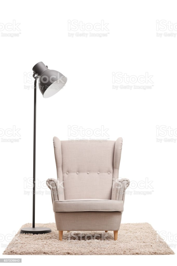 Classic armchair and a modern lamp on a carpet stock photo