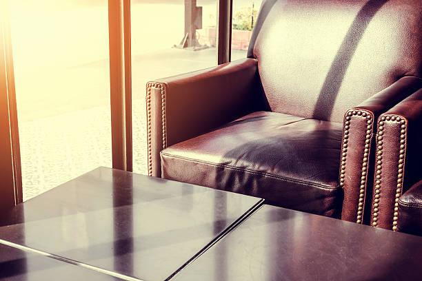 classic armchair with coffee table near window, vintage tone - diy leder stock-fotos und bilder
