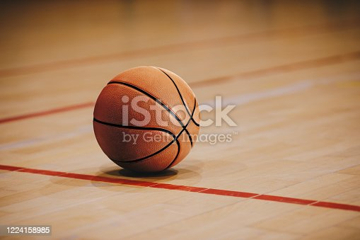 Classic Basketball on Wooden Court Floor Close Up with Blurred Arena in Background. Orange Ball on a Hardwood Basketball Court