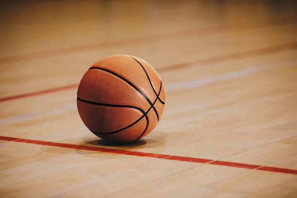 baloncesto clásico en el piso de la cancha de madera de cerca con la arena borrosa en el fondo. orange ball en una cancha de básquetbol de madera - basketball fotografías e imágenes de stock