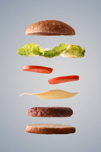 Hamburguesa de ternera clásico flotando en piezas sobre fondo gris - foto de stock