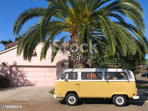 Classic beige and white vintage Volkswagen T1 camper van parked in front of pink house. San Diego, California, USA.