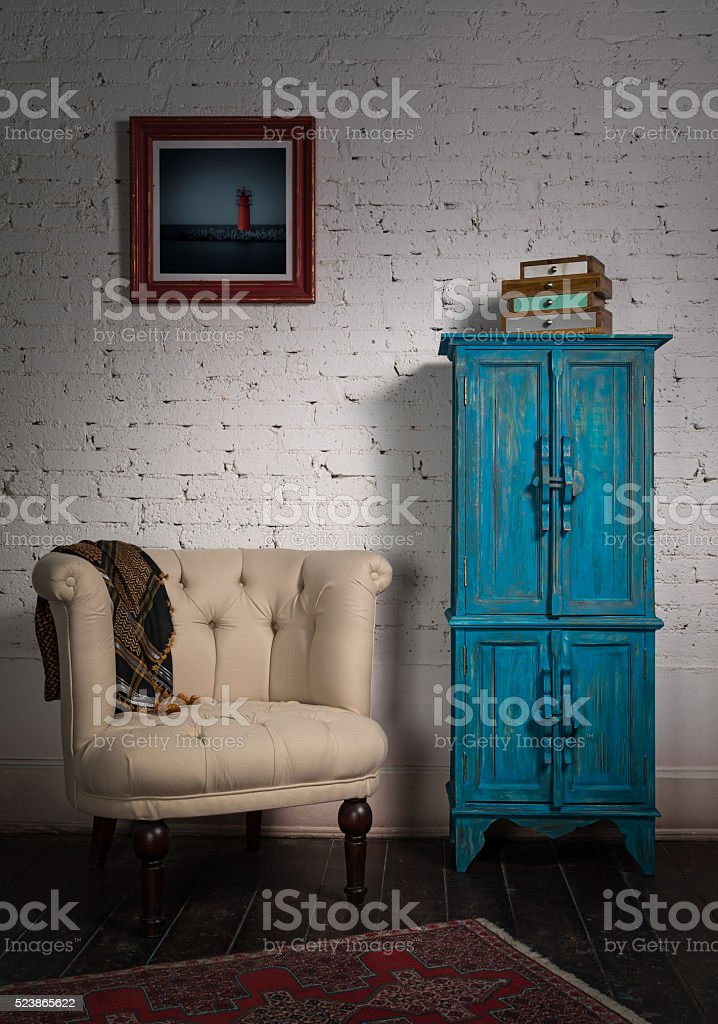 Classic beige armchair, blue vintage cupboard, scarf and painting stock photo