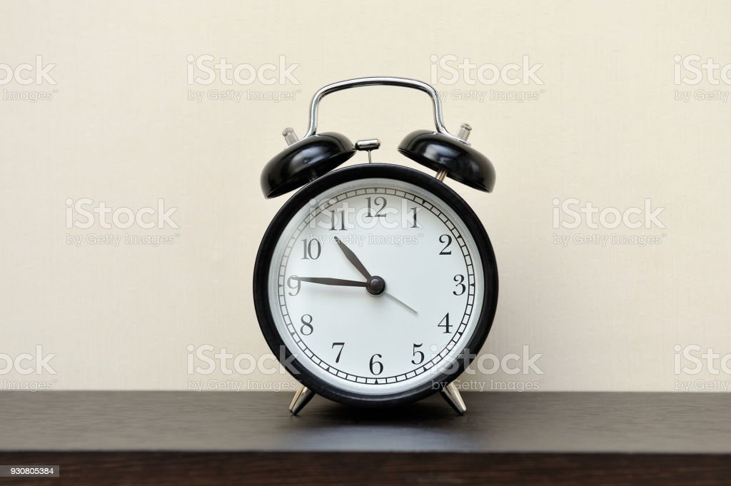 Classic black alarm clock in the home stock photo