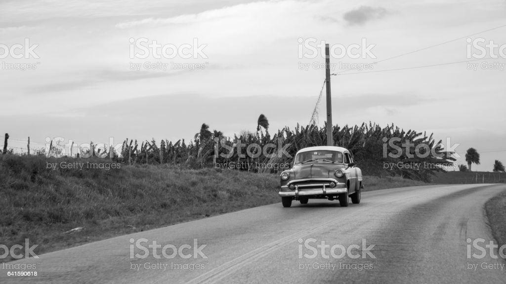 Classic black and white old car driving on Cuban highway. stock photo