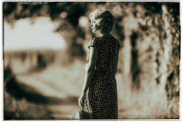 Classic black and white photo of 1930s fashion woman standing with handbag on rural pathway. stock photo