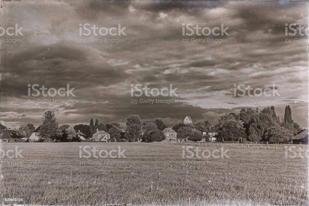 Classic black and white photo of dutch village with church tower over trees under stormy sky. stock photo